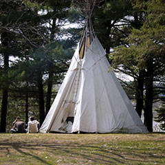 Colour photograph of a wigwam near a few trees. Three persons are sitting right beside it.
