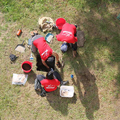 Colour photograph of an aerial view of the team digging an archeological test pit.