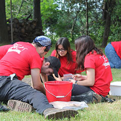 Colour photograph of five trainee archaeologists working in an excavation pit. They are all wearing red shirts.