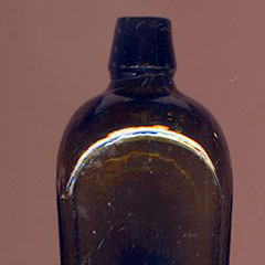 Colour photograph of a glass bottle.