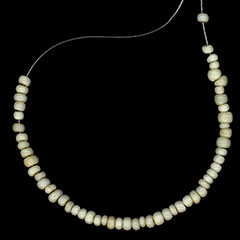 Colour photograph of a white glass beads necklace.