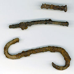 Colour photograph of three iron pieces: two nails and a hook.