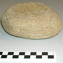 Colour photograph of a round and slightly flattened stone.