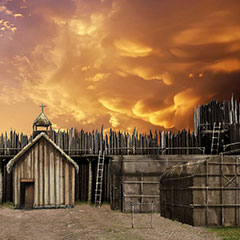Colour illustration of a couple of longhouses and a wooden church. The village is surrounded by a palisade. The sky is engulfed in flames.