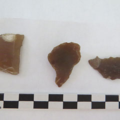 Colour photograph of three gunflints. They all have different shapes.