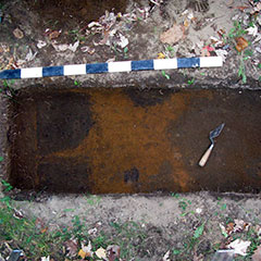 Colour photograph of a ground layer with a reddened area and of a trowel.