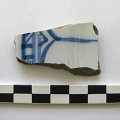 Colour photograph of a white earthenware shard with blue patterns.