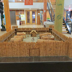Colour photograph of the model of the Fort d'Odanak, showing miniature longhouses. The model is located in the hall of the Museum.