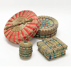 Colour photograph of four black ash baskets. They all have different shapes and sizes and are decorated in bright colors.